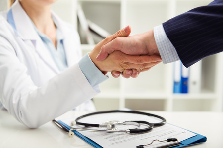 Foto de Woman doctor shaking hand with businessman in the office. Young medical specialist in uniform meeting partner for discussion. Shallow depth of field. - Imagen libre de derechos