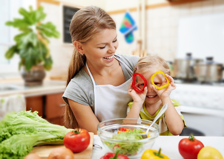 Photo pour Smiling mummy and her cute daughter having fun cooking vegetarian dinner. Little child playing with pepper rings while preparing salad. - image libre de droit