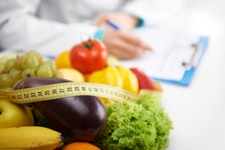 Foto de Healthy nutrition concept. Close-up of fresh vegetables and fruits with measuring tape lying on doctor's desk. - Imagen libre de derechos