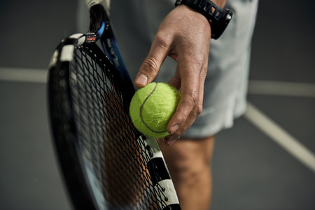Foto per Close-up of male hand holding tennis ball and racket. Professional tennis player starting set. - Immagine Royalty Free