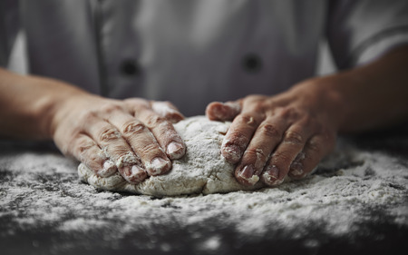 Photo pour Close-up of woman baker hands kneading the dough on black board with flour powder. Concept of baking and patisserie. - image libre de droit