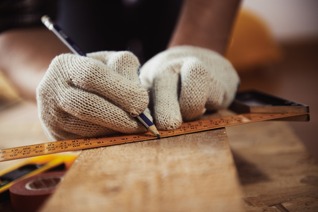 Photo pour Construction work. Woodwork. Male builder marking point on plank sitting on the floor. - image libre de droit