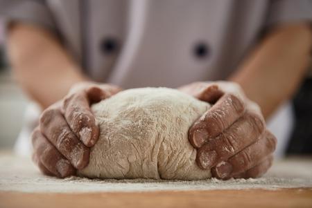 Foto de Close-up of woman baker hands kneading the dough on black board with flour powder. Concept of baking and patisserie. - Imagen libre de derechos