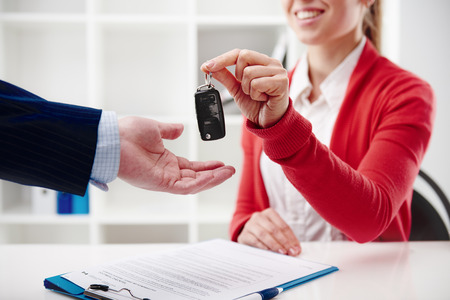 Photo pour Car rent or sale. Rental agent giving automobile key to customer in the office. - image libre de droit