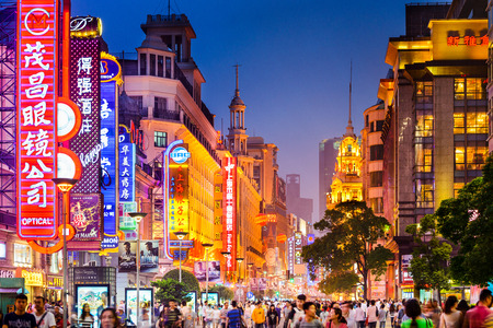 Photo pour SHANGHAI, CHINA - JUNE 16, 2014: Neon signs lit on Nanjing Road. The area is the main shopping district of the city and one of the world's busiest shopping streets. - image libre de droit