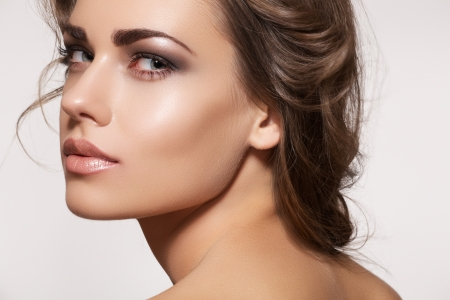 Foto de Glamour portrait of beautiful woman model with fresh daily makeup and romantic wavy hairstyle. Fashion shiny highlighter on skin, sexy gloss lips make-up and dark eyebrows  - Imagen libre de derechos