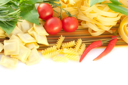 Spaghetti with red pepper, a basil and a tomato on a white background