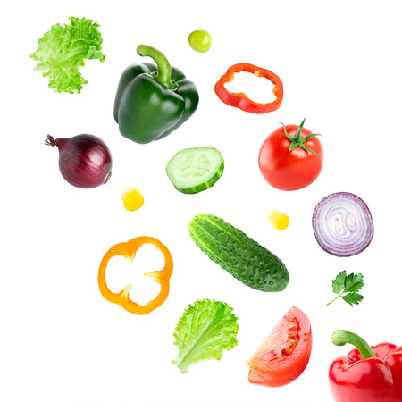 Falling fresh vegetables on white background