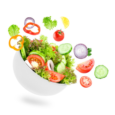Photo for Fresh salad. Mixed falling vegetables in bowl on white background - Royalty Free Image