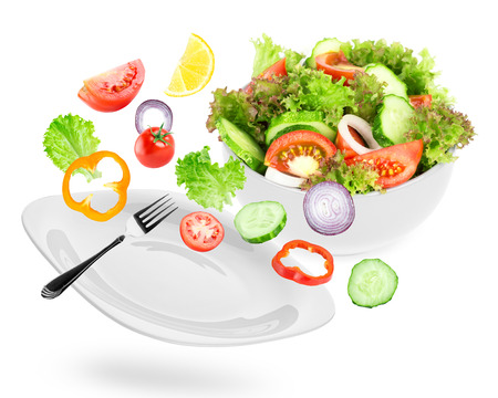 Fresh salad. Mixed falling vegetables in plate on white background