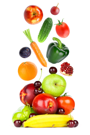 Fresh fruits and vegetables falling on white background