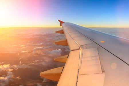 Foto de Aerial view of airplane flying above shade clouds and sky from an airplane fly during the sunset. View from the plane window of emotional moment during international travel around the world. - Imagen libre de derechos