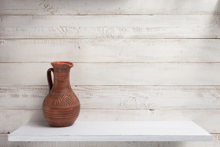 Photo pour clay jug at shelf on white wooden plank background - image libre de droit