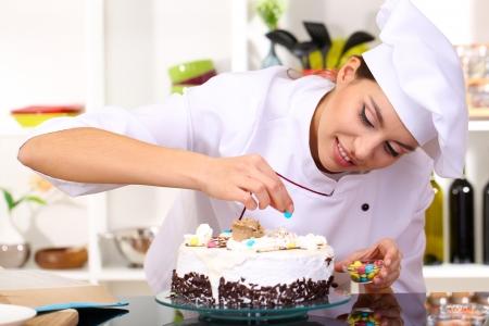 Photo pour Young woman chef cooking cake in kitchen - image libre de droit
