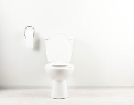 Foto de White toilet bowl and toilet paper in a bathroom - Imagen libre de derechos