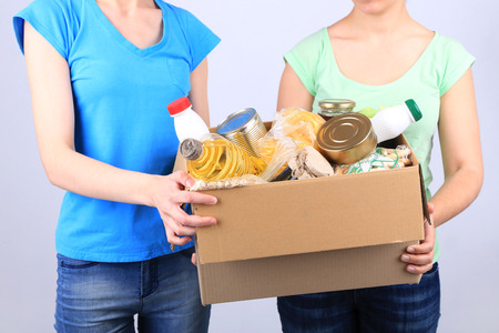 Photo pour Volunteers with donation box with foodstuffs on grey background - image libre de droit