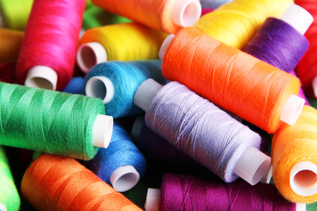 Foto de Multicolor sewing threads on wooden background - Imagen libre de derechos