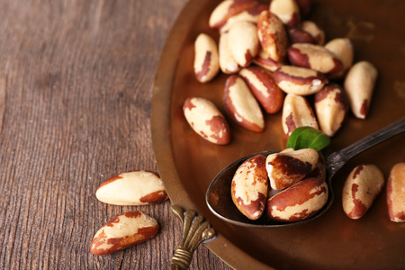 Photo for Tasty brasil nuts on salver, on wooden background - Royalty Free Image