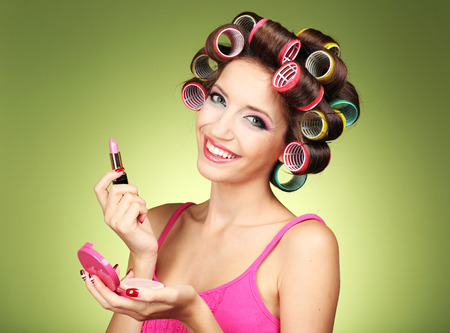 Photo pour Beautiful girl in hair curlers on green background - image libre de droit