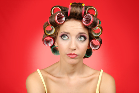 Photo pour Beautiful girl in hair curlers on red background - image libre de droit