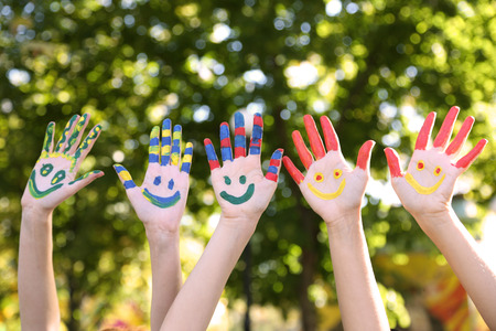 Photo pour Smiling colorful hands on natural background - image libre de droit