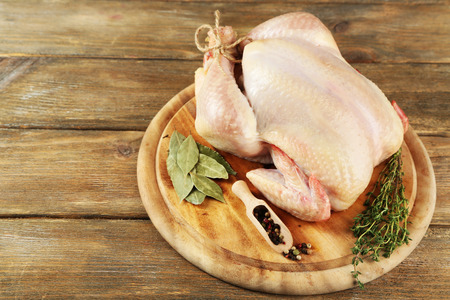 Photo pour Raw chicken on wooden table - image libre de droit