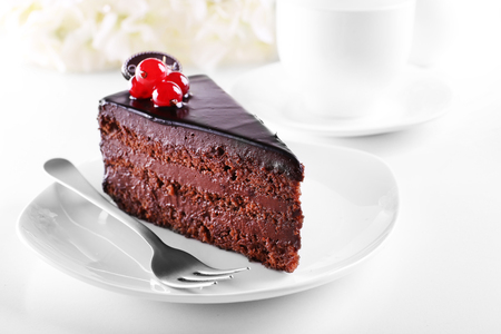 Photo for Delicious chocolate cake on plate on table on light background - Royalty Free Image