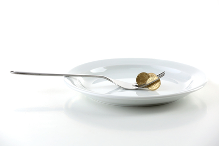 Foto de Coins on plate with fork isolated on white - Imagen libre de derechos