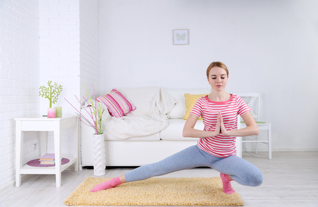 Foto de Young woman doing yoga at home - Imagen libre de derechos