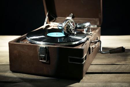 Foto für Gramophone with vinyl record on wooden table on dark background - Lizenzfreies Bild