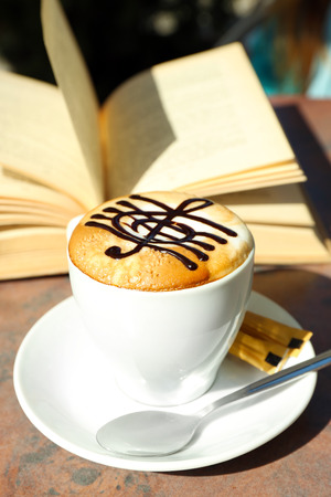 Photo pour Cups of cappuccino with treble clef on foam  and book on table in cafe - image libre de droit