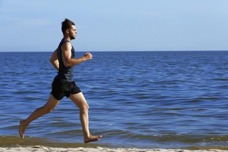 Photo pour Young man jogging on beach - image libre de droit