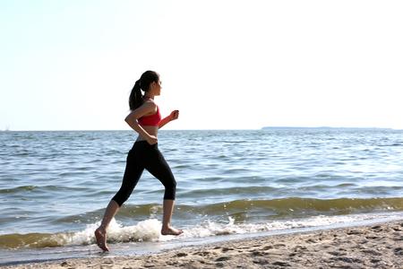 Photo pour Young woman jogging on beach - image libre de droit