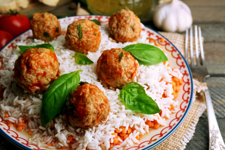 Photo for Meat balls in tomato sauce with boiled rice and lentil, wooden spoon on wooden background - Royalty Free Image