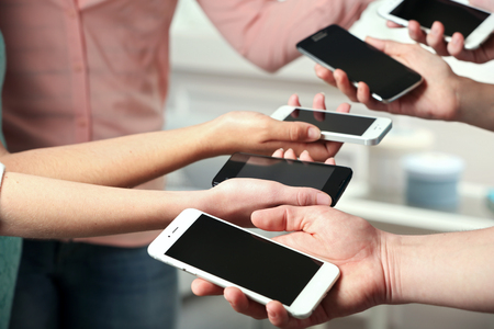 Photo for Many hands holding mobile phones close up - Royalty Free Image