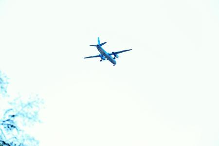 Foto de A grey airplane flying on a clear pale blue sky background - Imagen libre de derechos