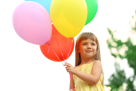 Photo for Little girl with balloons outside - Royalty Free Image