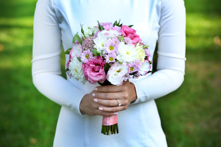 Photo for Beautiful wedding bouquet in hands of bride on nature background - Royalty Free Image