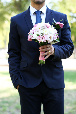 Photo for Groom holding wedding bouquet outdoors - Royalty Free Image