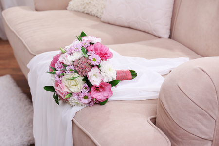 Photo for Wedding bouquet and bridesmaid dress on sofa in room - Royalty Free Image
