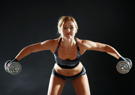 Photo for Athletic woman with dumbbells on dark background - Royalty Free Image