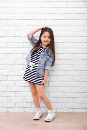 Foto de Little girl on a white brick wall background - Imagen libre de derechos