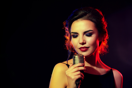 Photo for Portrait of beautiful singing woman on dark background - Royalty Free Image