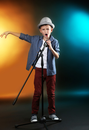Photo for Little boy singing with microphone on a dark lighted background - Royalty Free Image