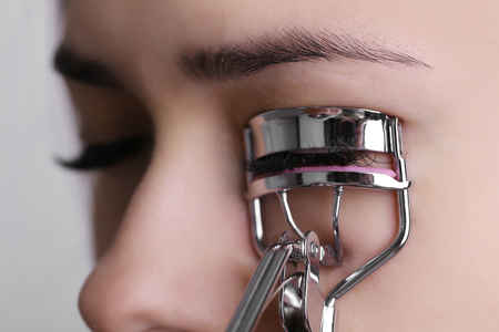 Photo pour Woman corrects eyelashes with curling tongs, close up - image libre de droit