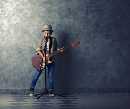 Photo for Little boy playing guitar and singing with microphone on a grey wall background - Royalty Free Image