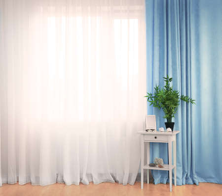 Photo pour Small white table with green plant and frame on curtain background - image libre de droit