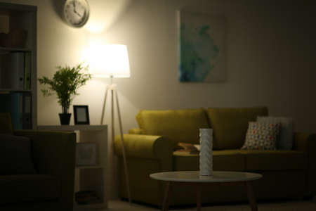 Photo pour Living room interior with lighted lamp, table and green sofa - image libre de droit