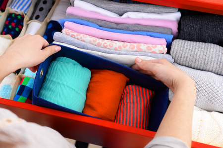 Photo pour Woman folding clothes into chest of drawers closeup - image libre de droit