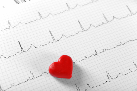 Foto de Cardiogram chart with small red heart on table closeup - Imagen libre de derechos